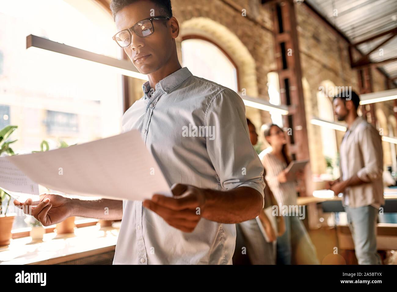 Arbeiten am neuen Projekt. Junge afro-amerikanische Mann in legere Kleidung die Analyse von Dokumenten, während im modernen Büro stehend Stockfoto