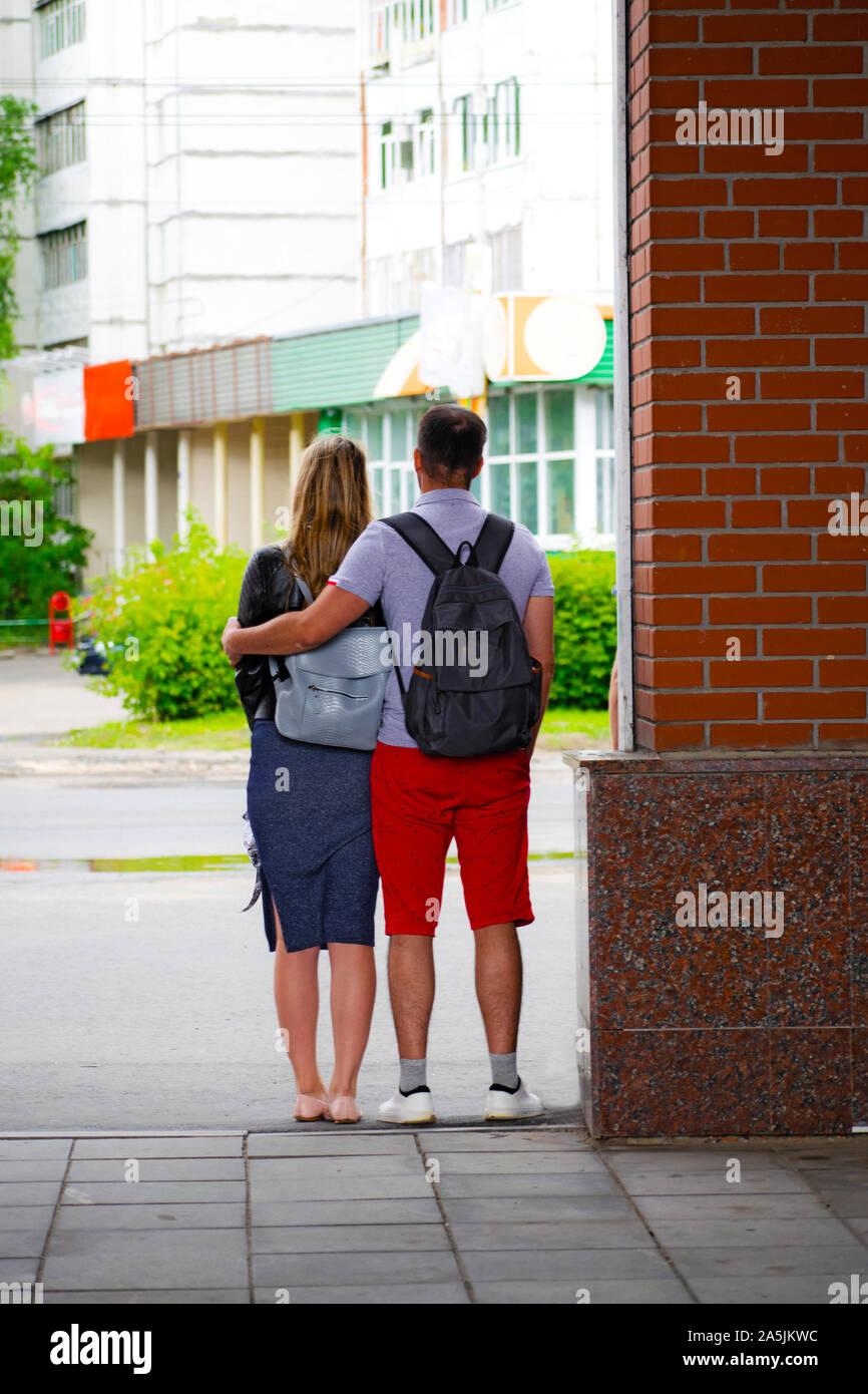 Rückansicht des schönen Paares Umarmung und Blick im Freien. Stockfoto