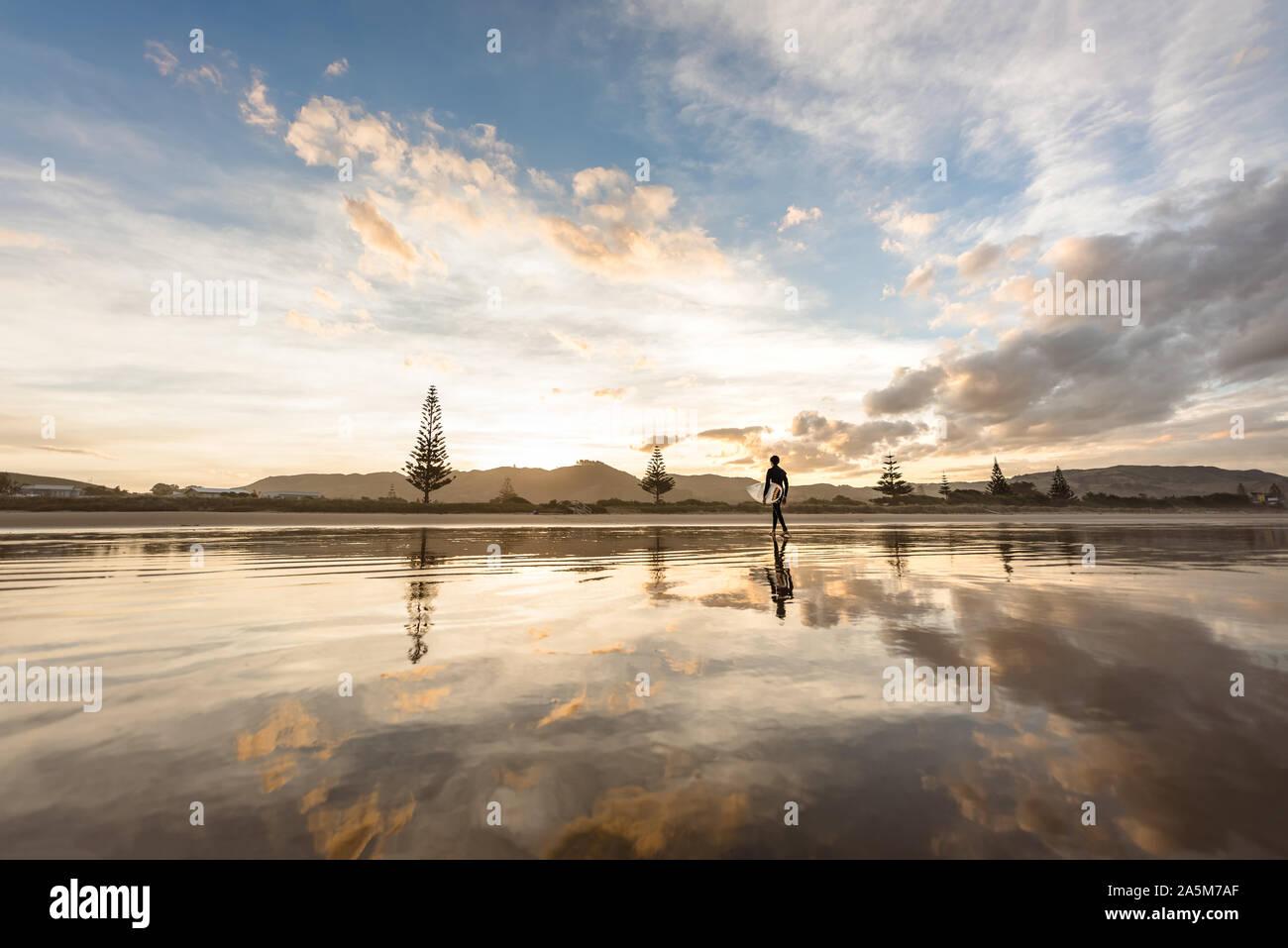 Jugendlich Junge mit Surfbrett zu Fuß am Strand bei Sonnenuntergang Stockfoto