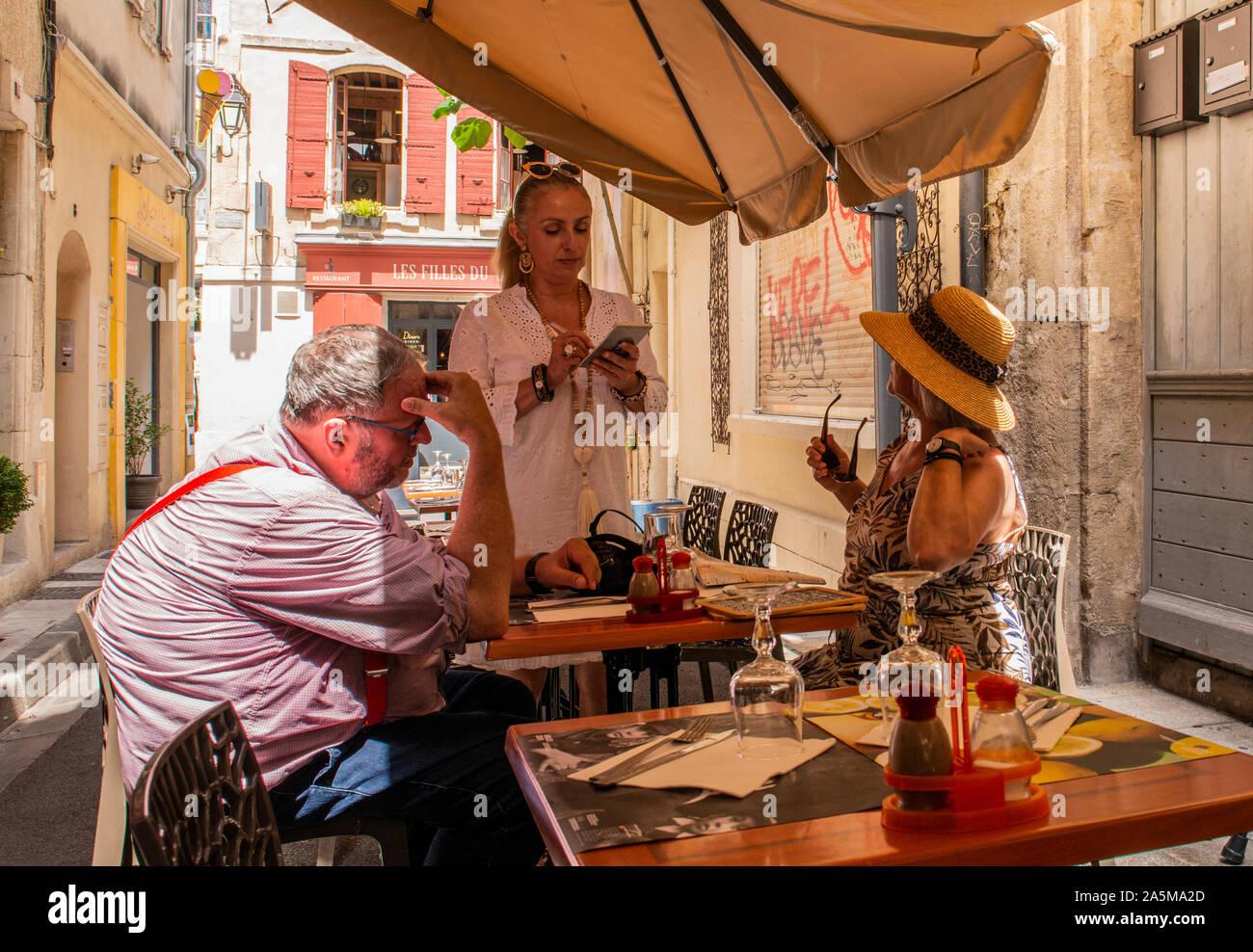 Kellnerin das Essen Aufträge von Kunden im Cafe, Arles, Frankreich Stockfoto
