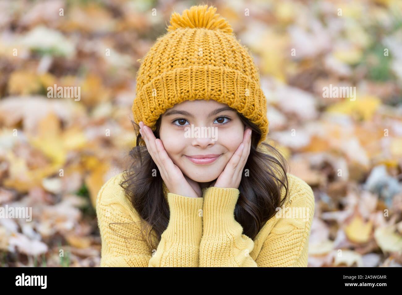 Warme wollmütze Zubehör. Mädchen lange Haare glückliches Gesicht Herbst Natur Hintergrund. Schöne Saison. Wärmsten halten in diesem Herbst. Kind in gelben Hut im Freien. Herbst Skin Care Routine. Kid tragen Sie warme Strickmütze. Stockfoto