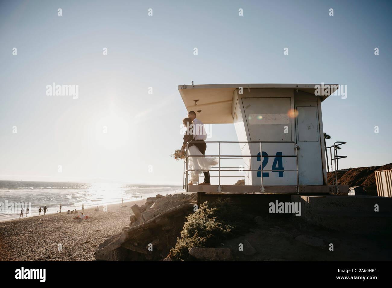 Braut und Bräutigam an lifeguard Hütte am Strand bei Sonnenuntergang Stockfoto