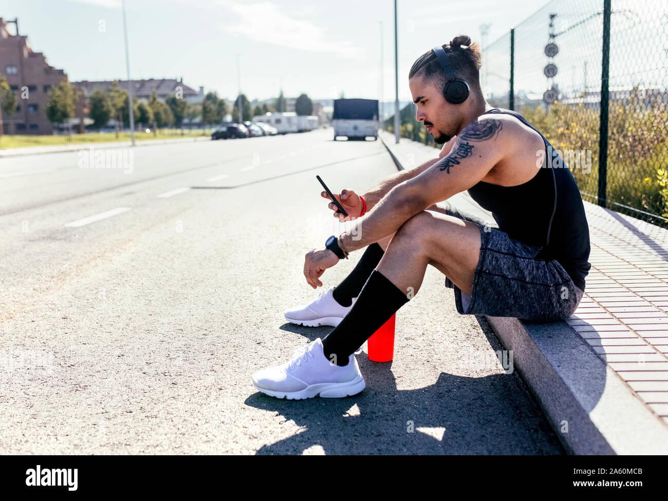 Sportlichen jungen Mann mit Smartphone und Kopfhörer am Straßenrand sitzen Stockfoto