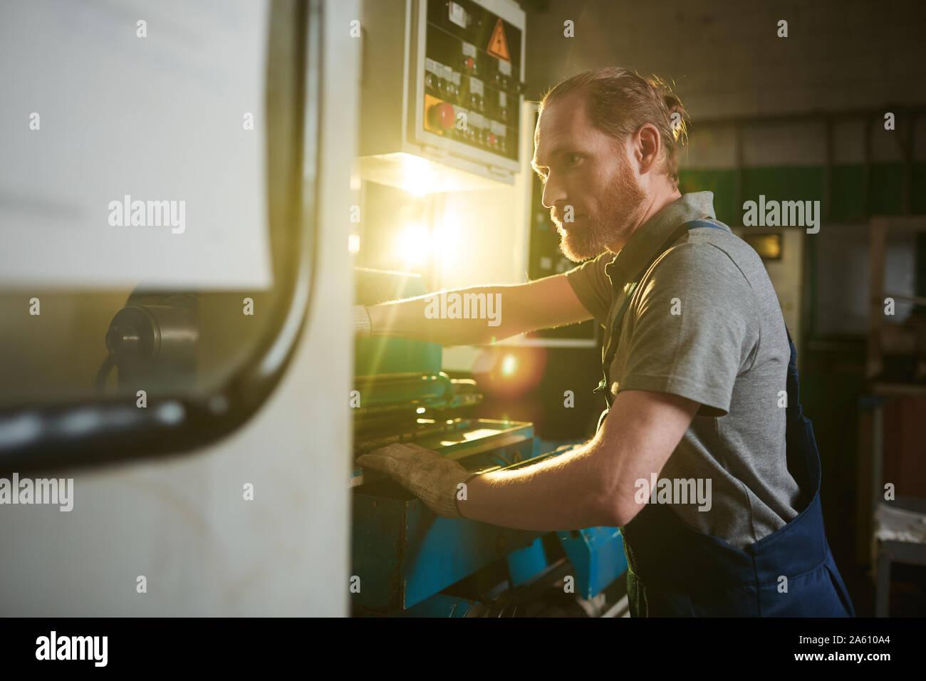 Arbeiter in Latzhosen konzentriert sich auf seine Arbeit, die er stehen und arbeiten an der Drehbank in der Anlage Stockfoto