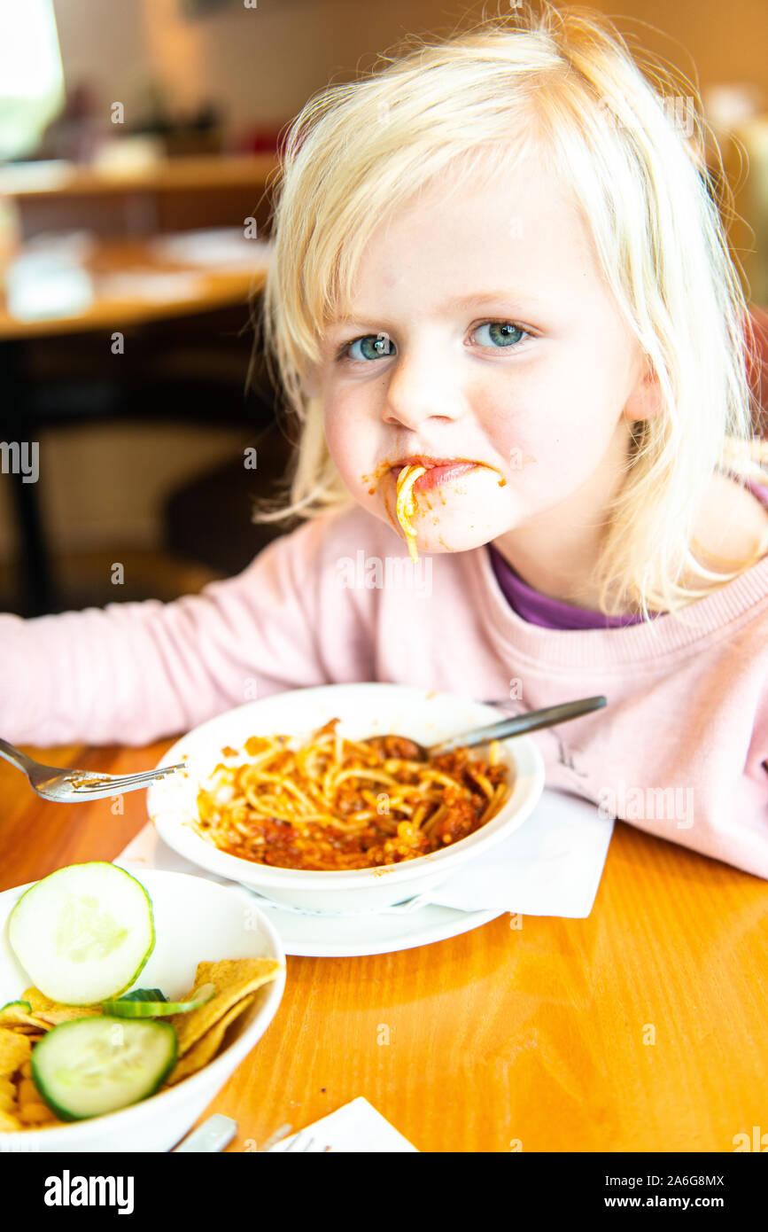 Eine schöne, süße kleine blonde Mädchen Spaß haben beim Essen Spaghetti Bolognese, spagbol in einem Restaurant Stockfoto