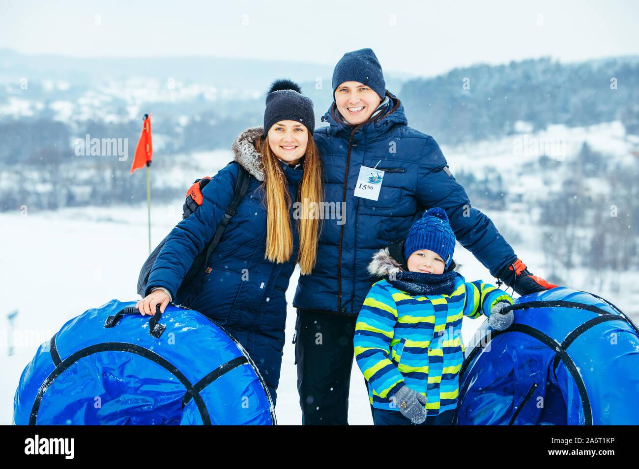 Junge Familie mit Snow tubes posieren. Winter Stockfoto