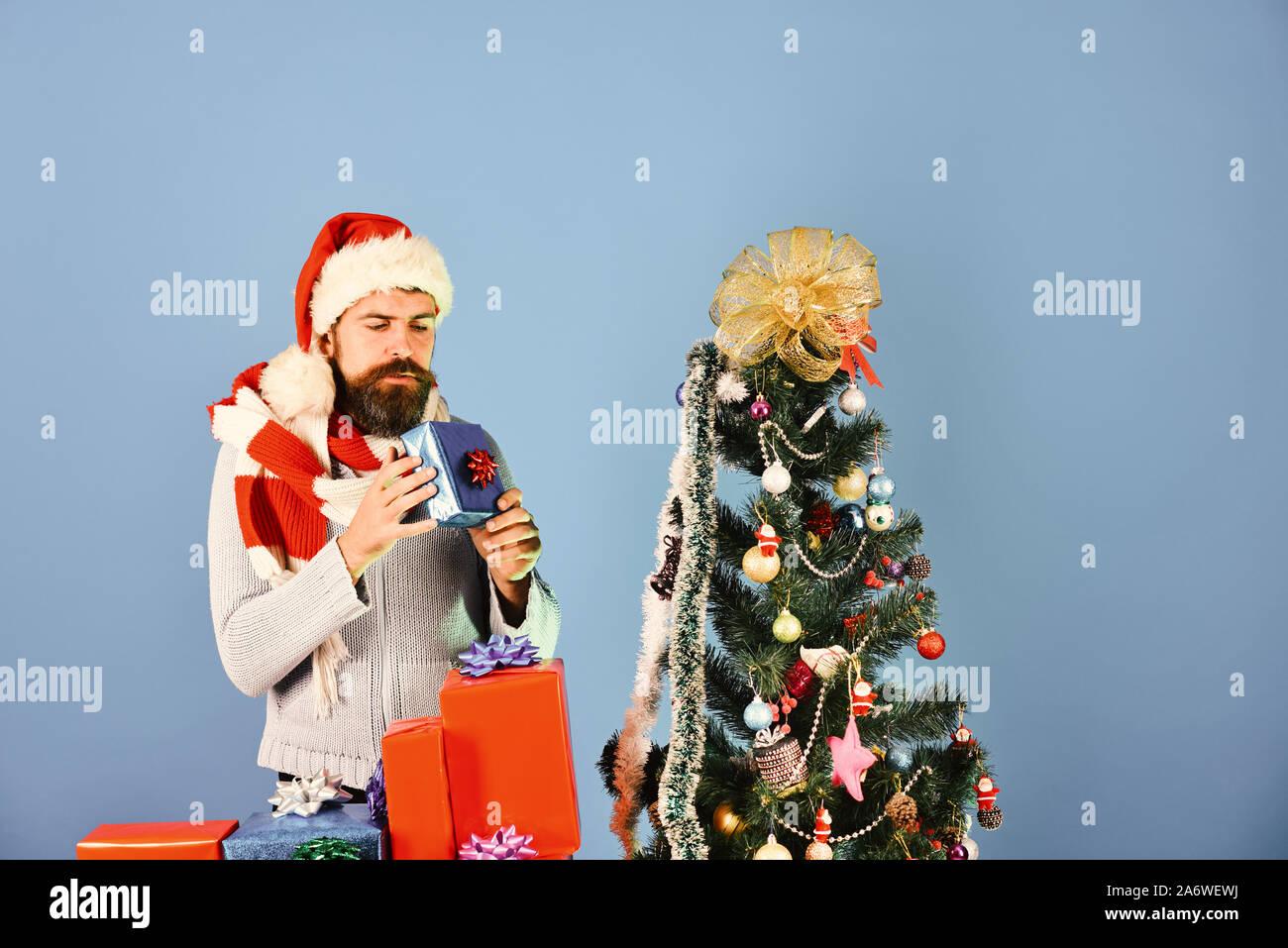 Mann mit Bart und neugierig Gesicht auf blauem Hintergrund. Kerl oder hipster Shopper in Red Hat mit Weihnachten Geschenkboxen. Weihnachten saisonale Rabatte Konzept. Santa öffnet Blau in der Nähe von geschmückten Baum Stockfoto
