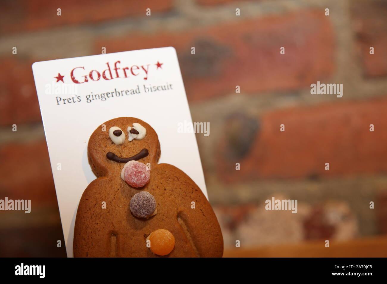 Godfrey, Prets Lebkuchen-Mann-Keks mit einem schlecht vereisten Auge vor Backstein-Hintergrund mit Kopierraum Stockfoto