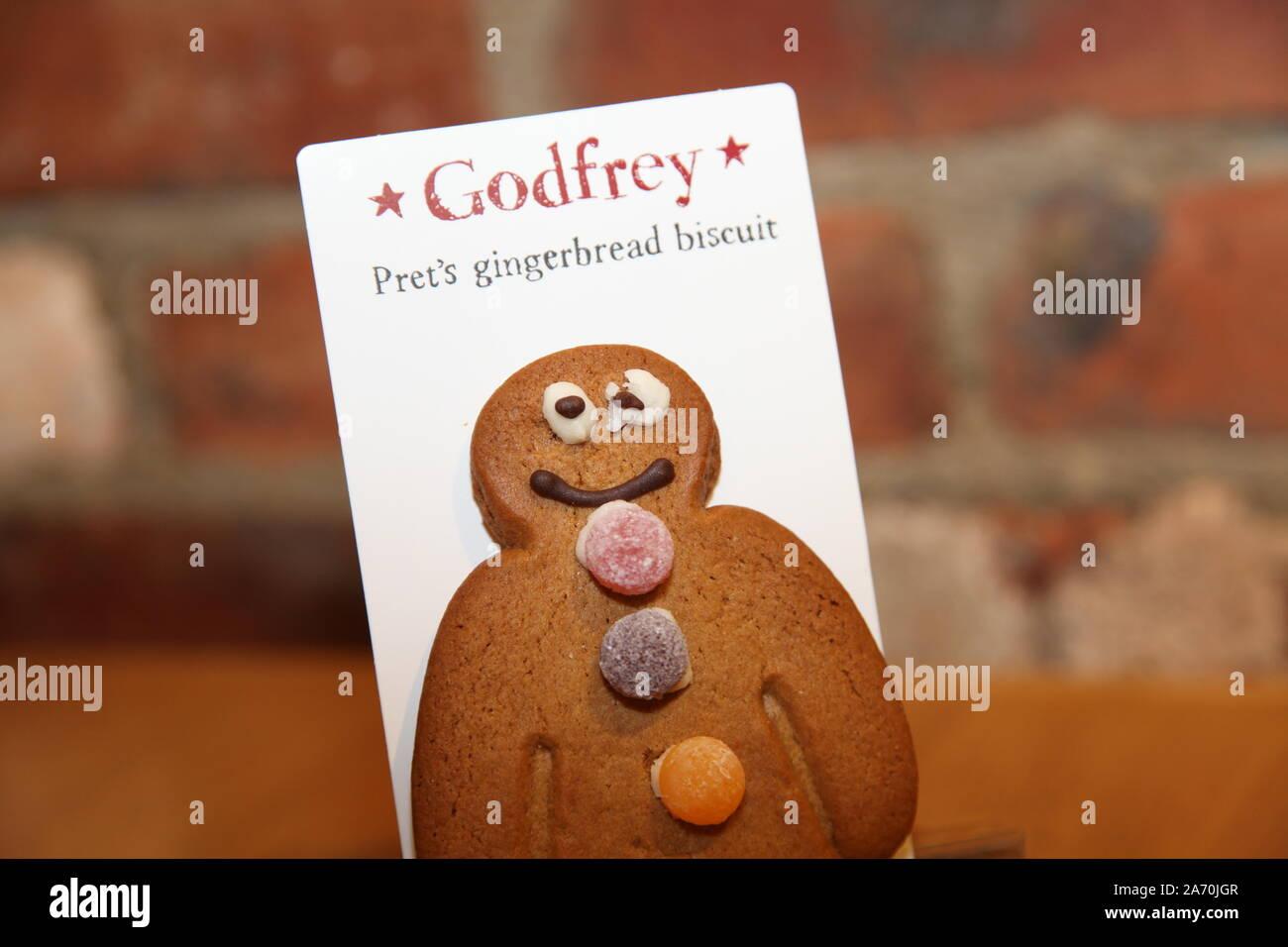Godfrey, Gingerbread Man Pret's Keks mit einem schlecht iced Auge gegen Ziegel Hintergrund Stockfoto