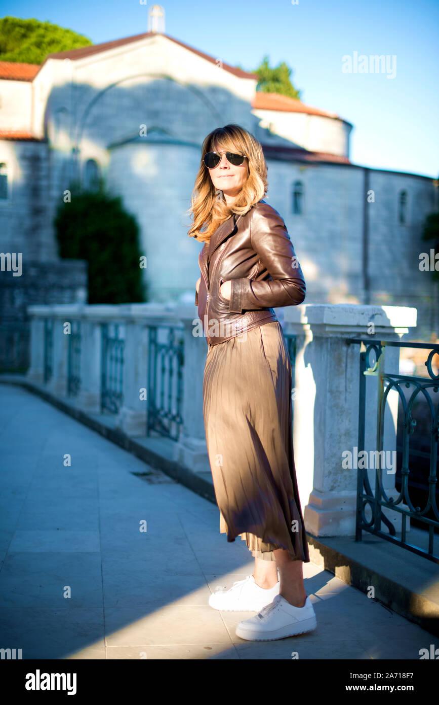 Volle Länge geschossen von glücklichen erwachsenen Frau lächelnd im Freien und gehen auf die Straße der Stadt. Hübsche Frau mit Sonnenbrille und Biker Jacke während Sie entspannen Stockfoto