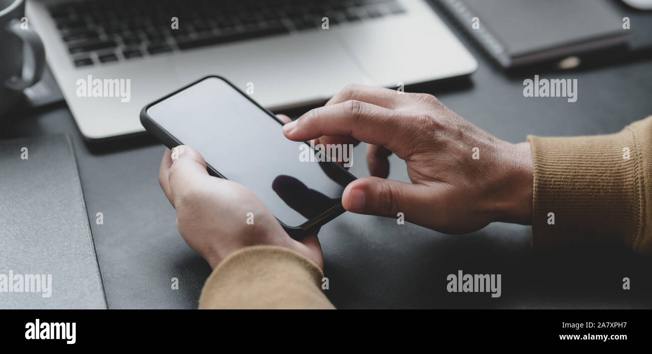 7/8 shot professioneller Geschäftsmann berühren Smartphone in seinen dunklen Luxus Büro Zimmer Stockfoto