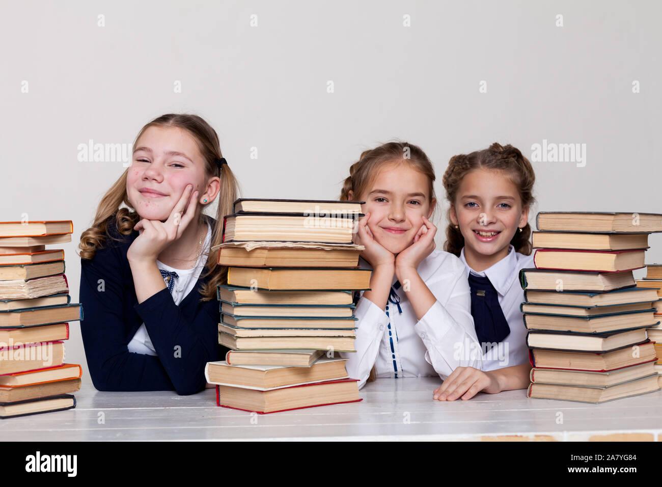 Drei schulmädchen Mädchen mit Büchern in der Bibliothek in der Klasse an der Rezeption Stockfoto