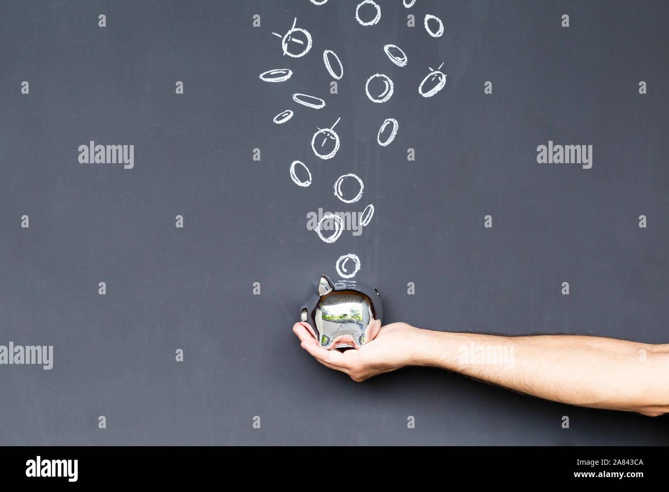Konzept der Geld sparen mit einem silberfarbenen Sparschwein in der Hand vor einer Tafel mit Hand gezeichnet Münzen statt Stockfoto
