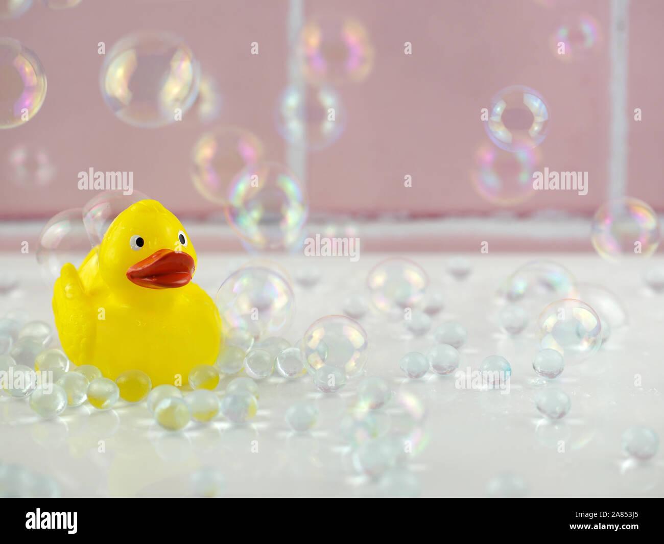 Gelbe Gummiente in Bad mit Blasen und rosa Kacheln Stockfoto