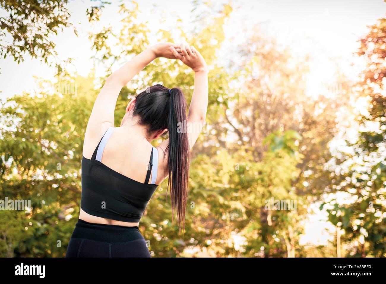 Schöne Frau zu tun Stretching Übungen auf dem Boden. Junge sportliche Frau, trainieren im Sommer Park. Stockfoto