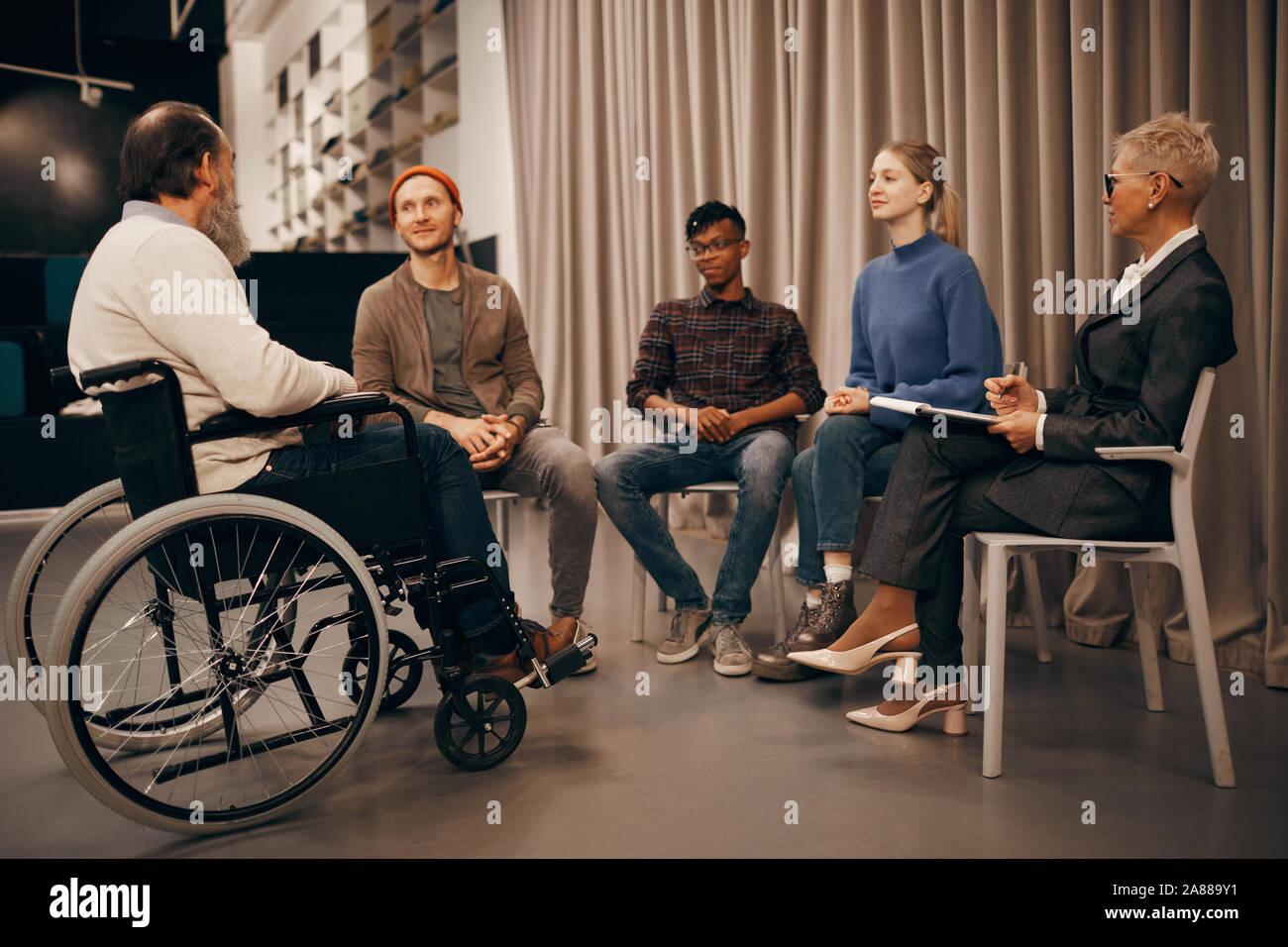 Gruppe von Geschäftsleuten sitzen auf Stühlen und hören zu den älteren Mann, der sitzt im Rollstuhl an der Konferenz Stockfoto