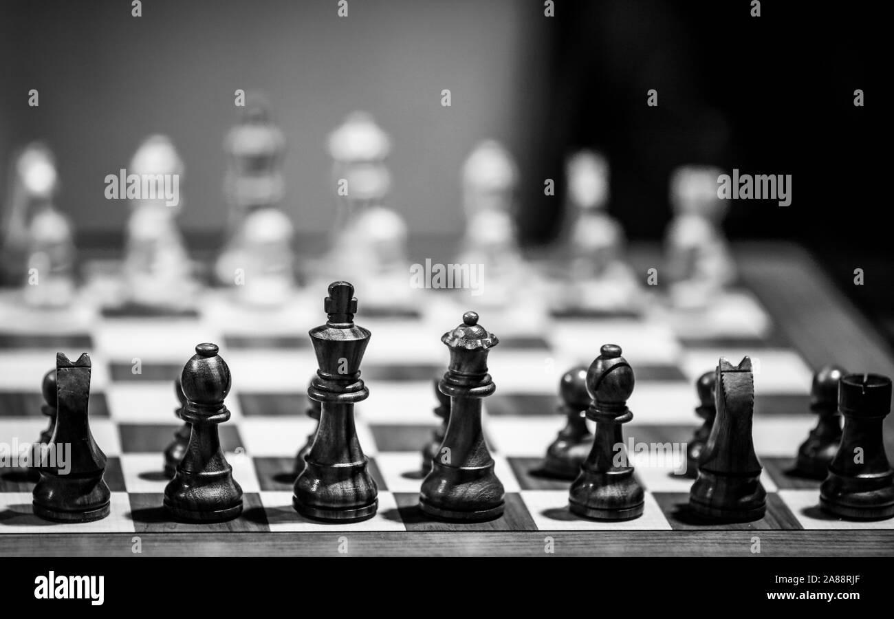 Monochrome flache Tiefenschärfe (selektive Fokus) Bild mit Holz- Schachfiguren auf einem holztisch vor einem professionellen Wettbewerb. Stockfoto