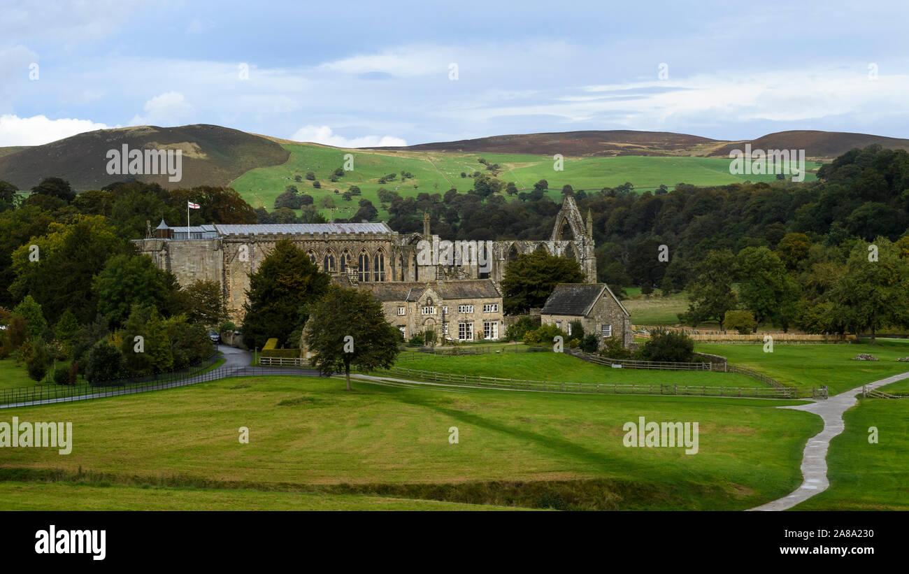 Malerische ländliche Blick über die alten, malerischen monastischen Ruinen von Bolton Abbey, Klosterkirche, Alte Pfarrhaus & gewundenen Pfad - Yorkshire Dales, England, UK. Stockfoto
