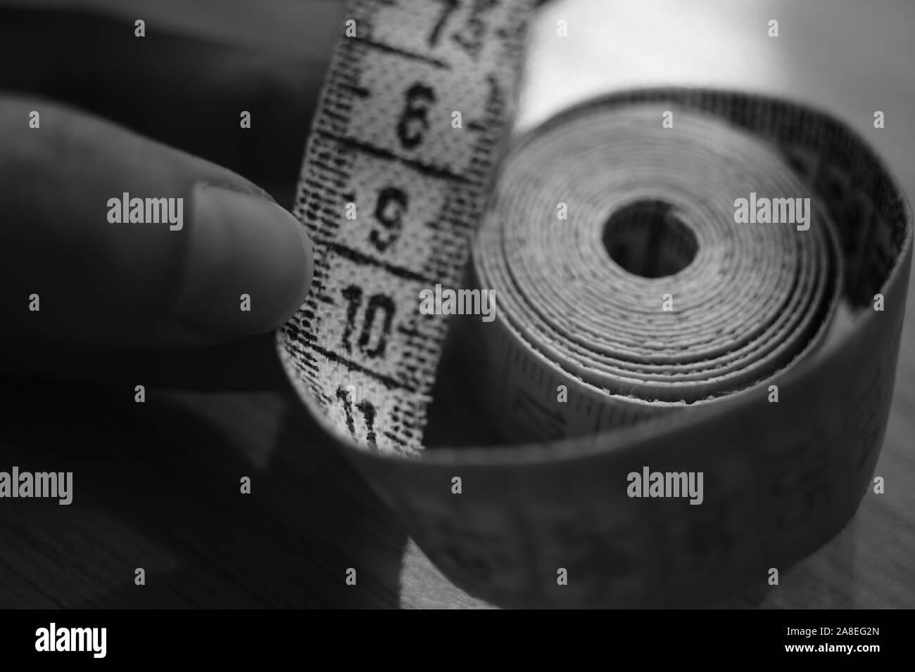 Maßband auf den menschlichen Finger. Schwarz-weiß Foto. Stockfoto
