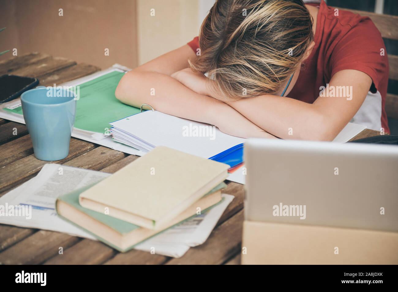 Müde Schüler Hausaufgaben zu Hause sitzen im Freien mit Schule Bücher und Zeitungen. Junge müde wegen der schweren studieren. Kind schlafend auf dem copybook nach l Stockfoto