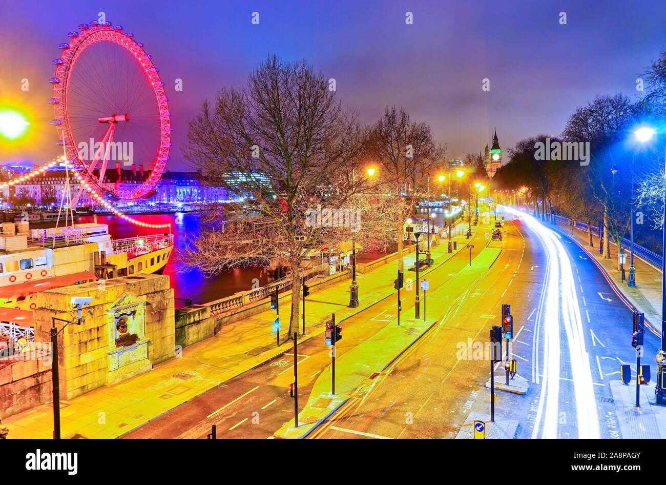 Blick auf die Häuser des Parlaments mit den nachts auf der Straße in London vorbeifahrenden Autos. Stockfoto