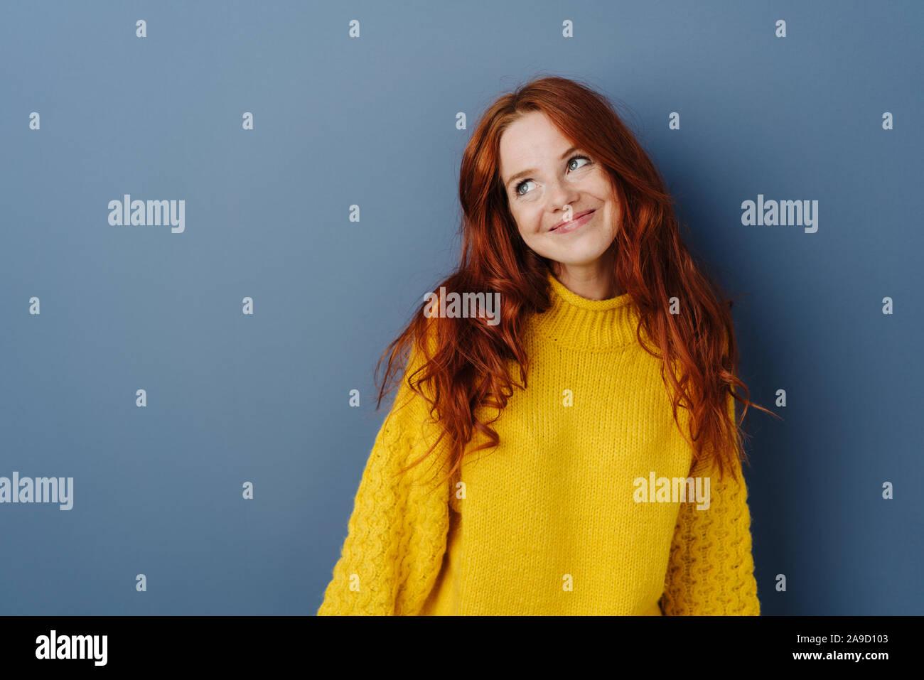 Simpering junge Frau mit einem coy Lächeln beiseite, mit einem Lächeln, als sie über einen blauen studio Hintergrund mit Kopie Raum flirtet Stockfoto