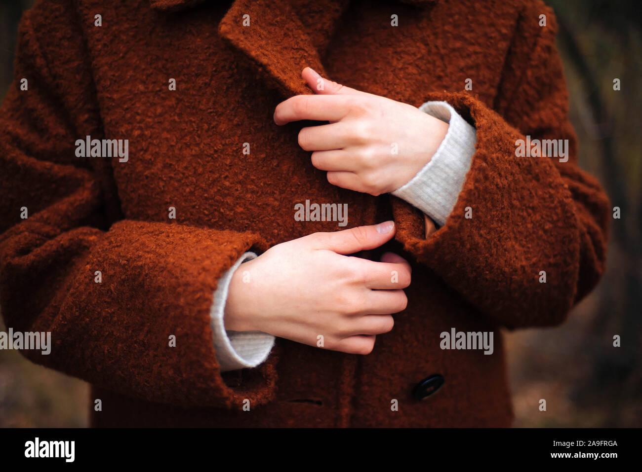 Nicht erkennbare weibliche Hände in hellen braunen Fell im Herbst Stockfoto