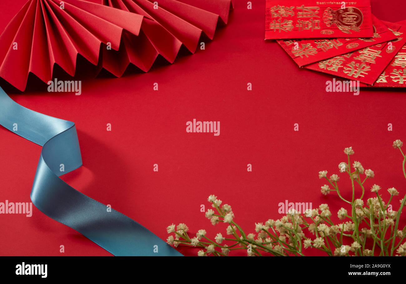 Der rote Hintergrund des Themas Chinesischen Neujahr, mit roten folding Fan und mit etwas Glück Geld, Blümchen und Blue Belt,Übersetzung:Wohlstand kann mit Euch. Stockfoto