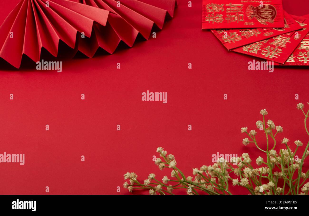 Der rote Hintergrund des Themas Chinesischen Neujahr, mit roten folding Fan und mit etwas Glück Geld, Blümchen, Übersetzung:kann Wohlstand mit Euch. Stockfoto