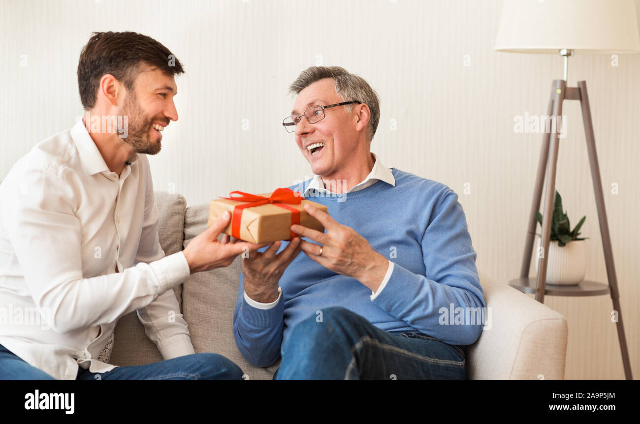 Reifen Sohn gratulieren älteren Vater Geschenk Sitzen auf einem Sofa Stockfoto