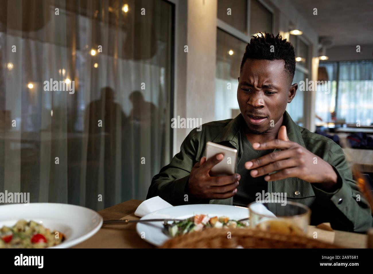 Junge enttäuscht überrascht afrikanische amerikanische Mann Messaging online, Kontrolle soziale Netzwerke im Cafe. Kopieren Sie Platz Stockfoto