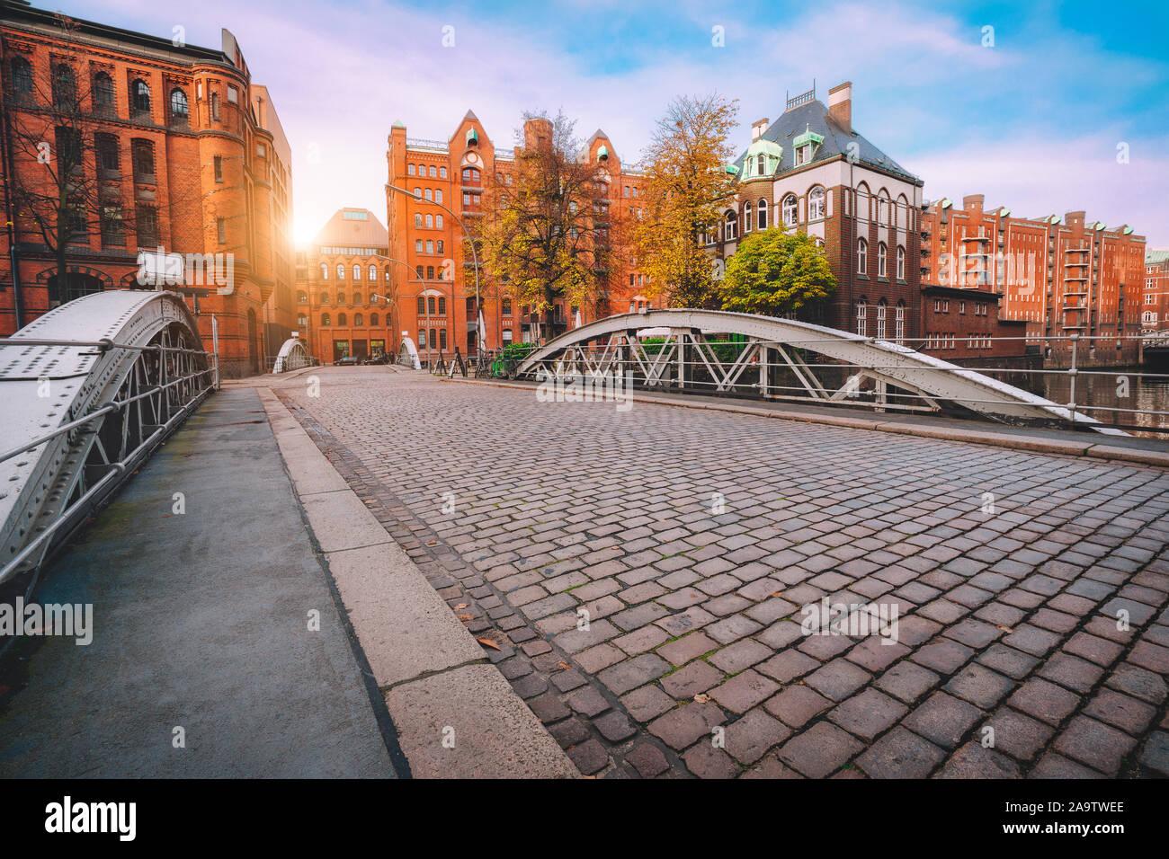 Bogenbrücke über die Kanäle hinweg mit Kopfsteinpflaster in der Speicherstadt in Hamburg, Deutschland, Europa. Historischen Backsteinbau von Golden Sunset light n Stockfoto