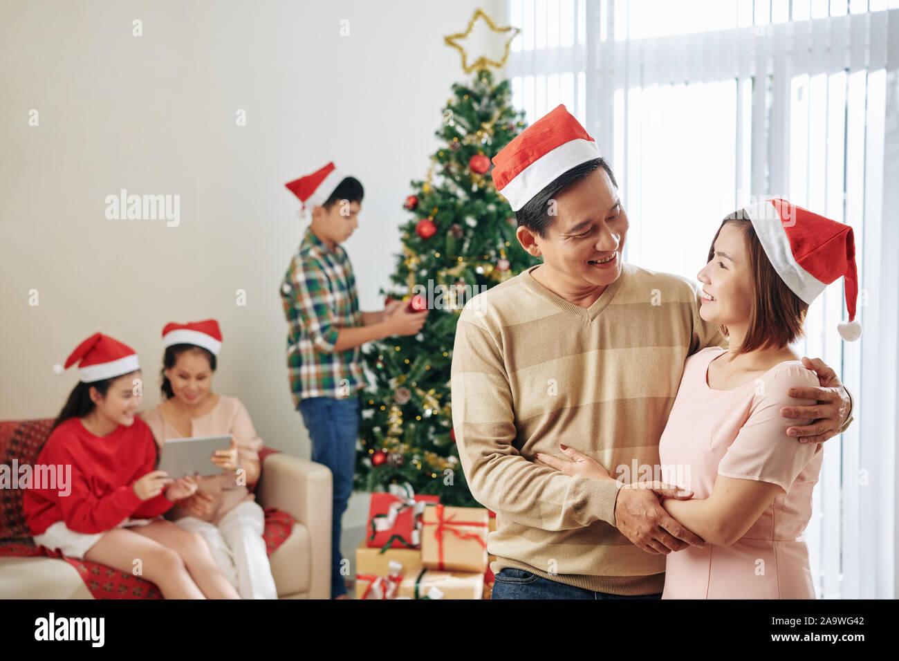 Lächelnd im mittleren Alter Mann und Frau umarmen und an jedem anderen suchen, wenn Ihre Familie Vorbereitung auf Weihnachten Feier Stockfoto