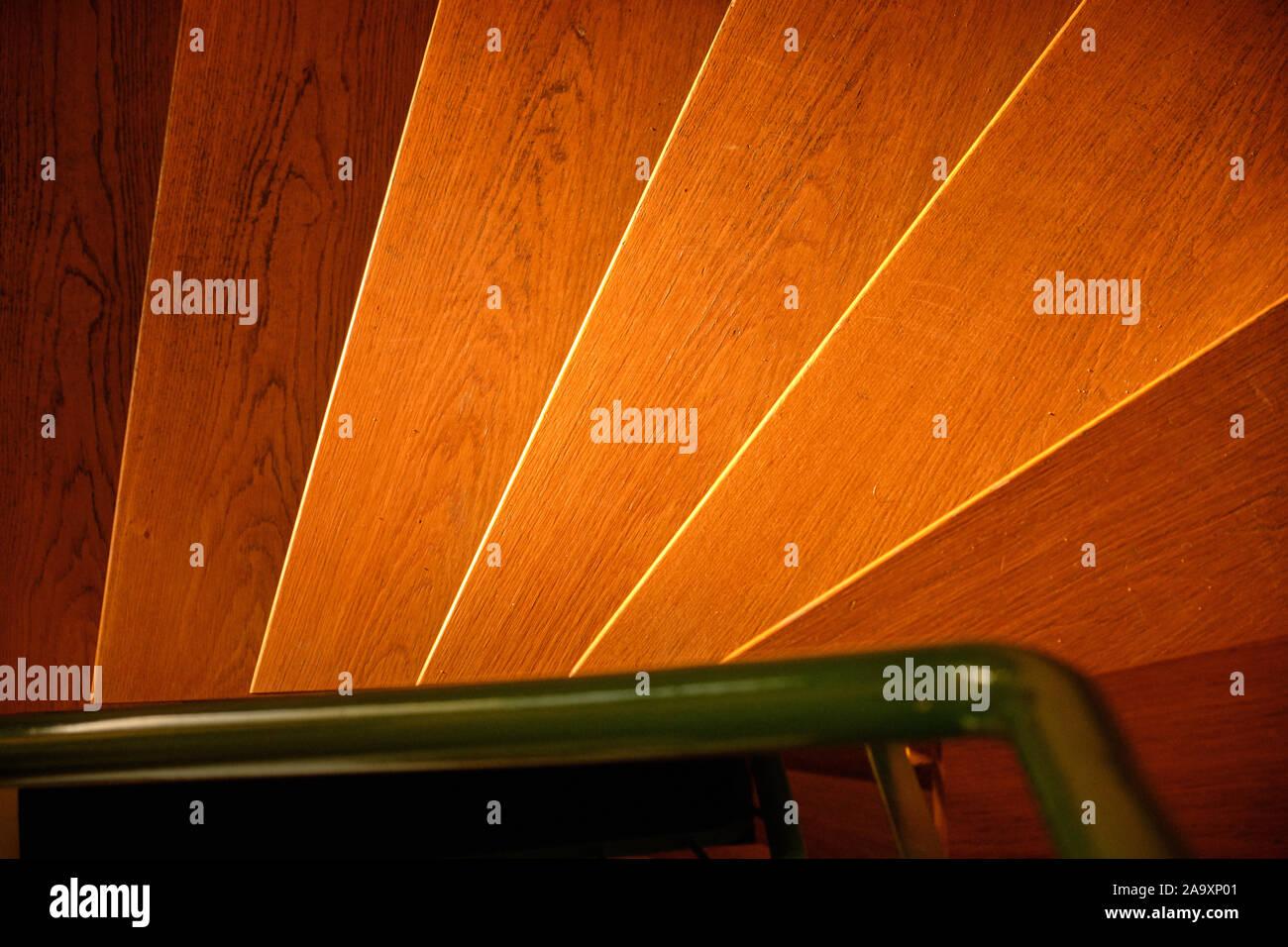 Abstrakte Shot mit einem Blick von oben auf das helle Holztreppe in der warmen Abendsonne in einem Haus und einem grünen Geländer aus Stahl Stockfoto