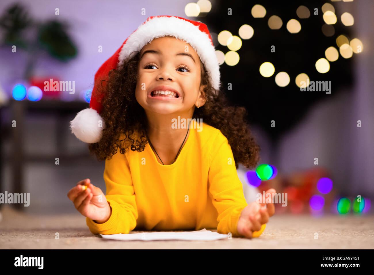 Emotionale afrikanische amerikanische Mädchen schreiben Brief an Santa Stockfoto
