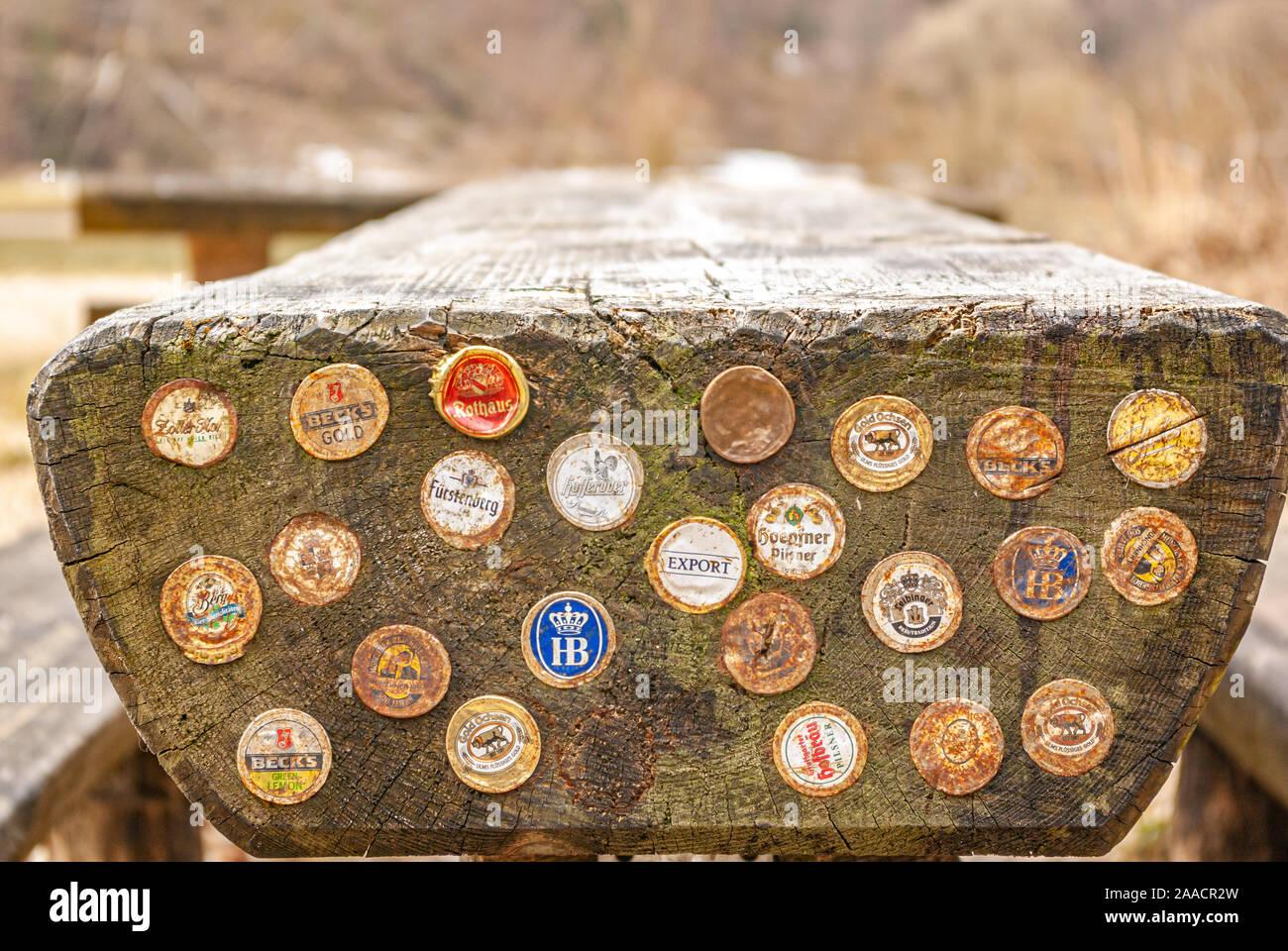 Kappen von verschiedenen deutschen Biermarken in die Front eines Rastplatz Sitzbank gehämmert. Stockfoto