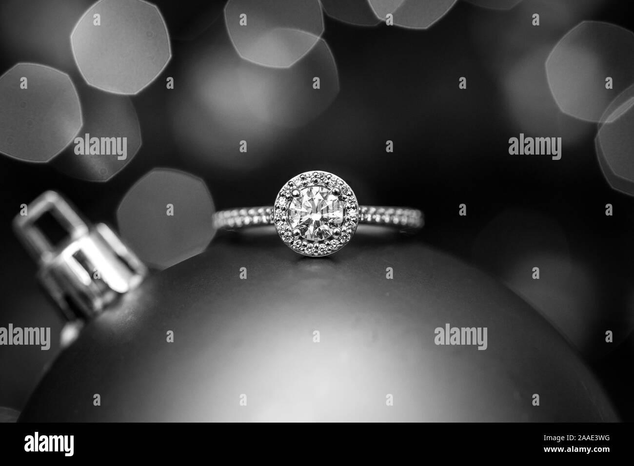 Verlobungsring auf a Christmas Ornament mit Licht im Hintergrund. Schwarz und Weiß. Stockfoto