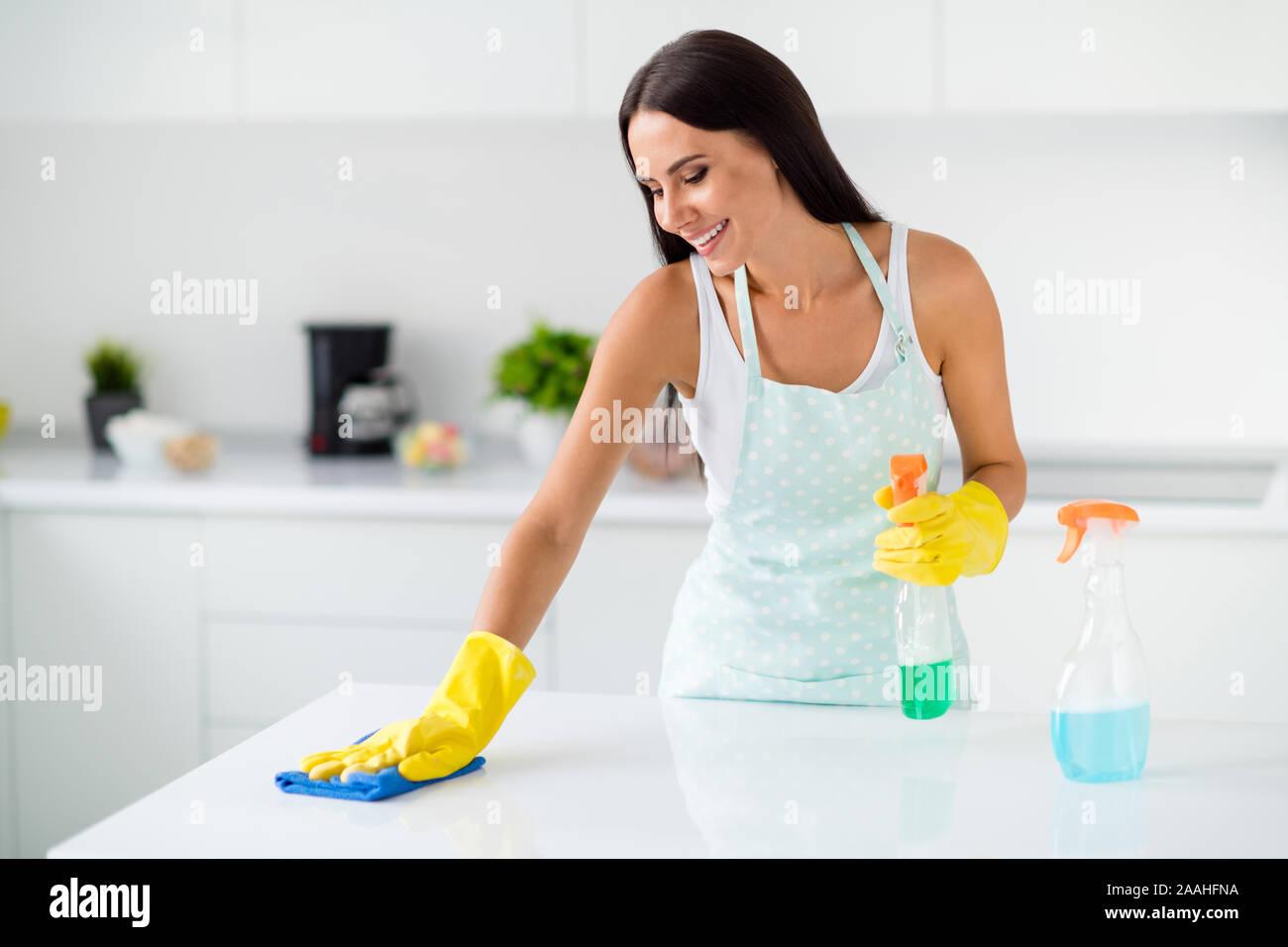 Portrait von positiven fröhliches Mädchen tragen gelbe Latex Wäsche polnischen Schreibtisch mit Waschmittel fühlen Inhalt in der Küche Licht house apartment Stockfoto