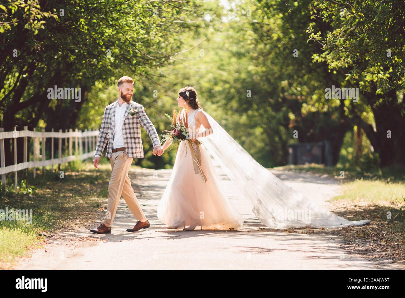 Schöne Hochzeit paar Holz Wald. Braut und Bräutigam, Follow me, Ehepaar, Frau in weißem Brautkleid und Schleier. Rustikal im Freien Liebesgeschichte Stockfoto