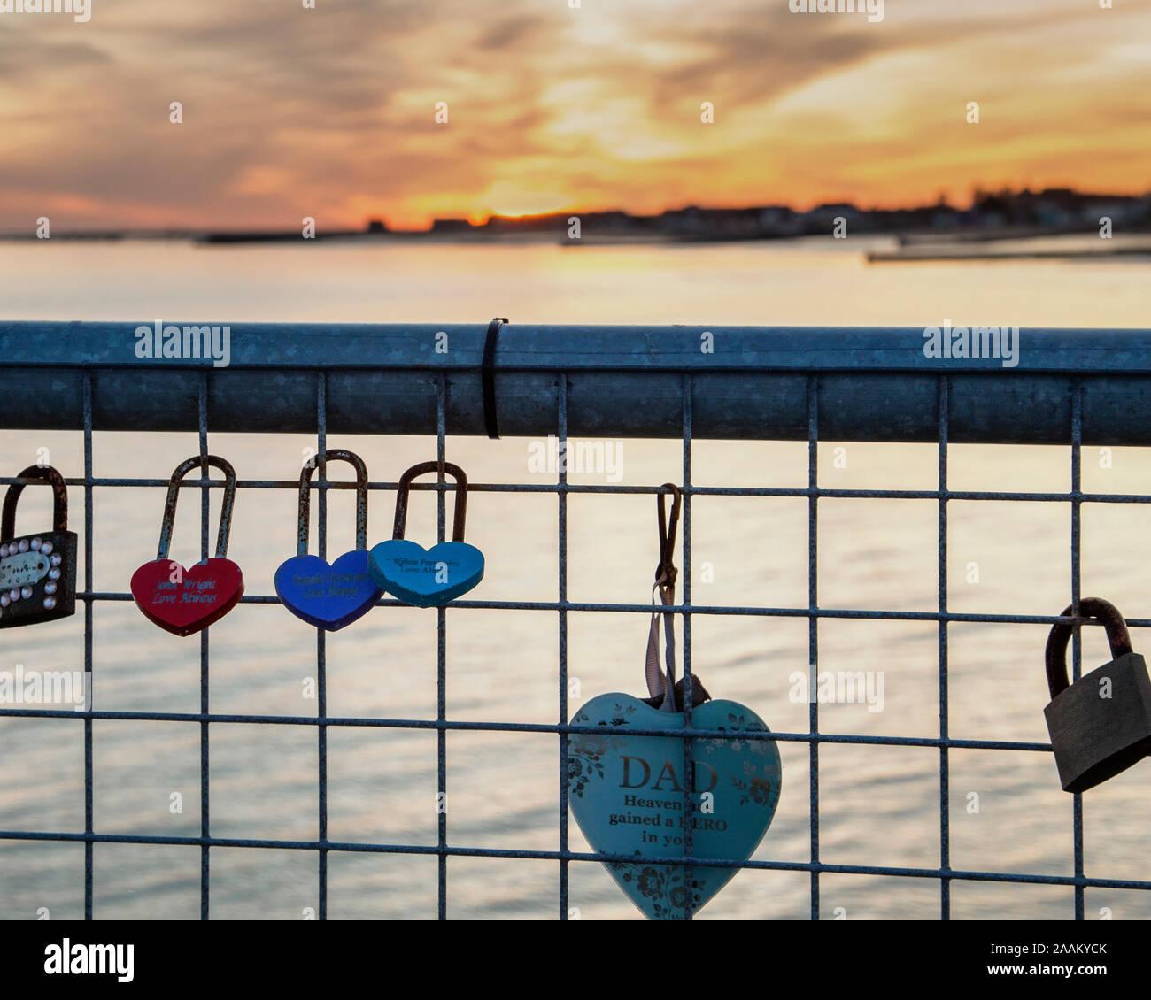 Liebe Schlösser angeschlossen an ein Geländer mit einem Sonnenuntergang in der Ferne. Konzept der Sonne, die auf eine Beziehung, die aus Liebe und oben brechen. Stockfoto