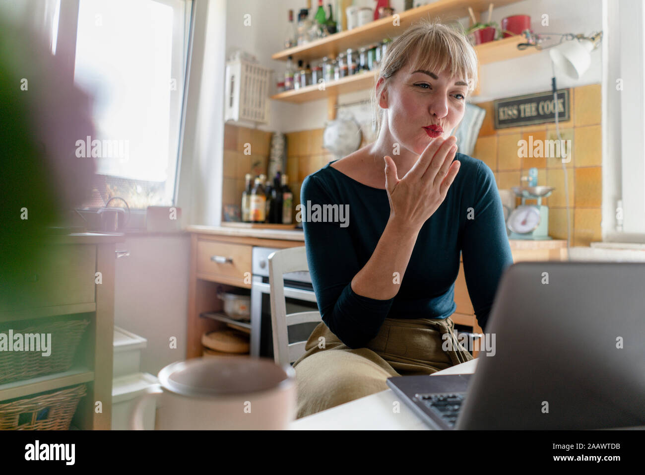 Porträt der jungen Frau mit Laptop in der Küche, bläst einen Kuss Stockfoto