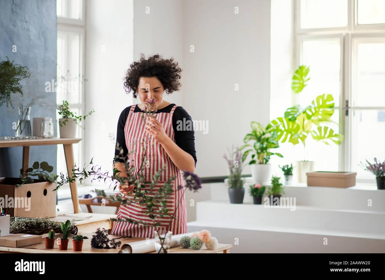 Lächelnde junge Frau riecht an der Pflanze in einem kleinen Laden Stockfoto