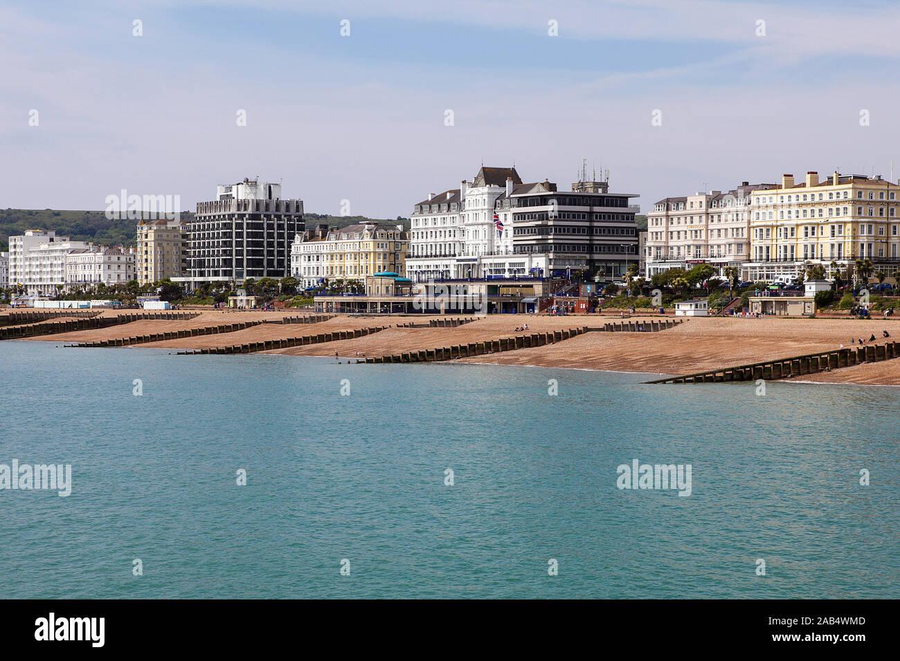 Küste Hotels und mehrere buhnen am Strand von Eastbourne, hier an einem bewölkten Tag gesehen im Mai 2019. Stockfoto
