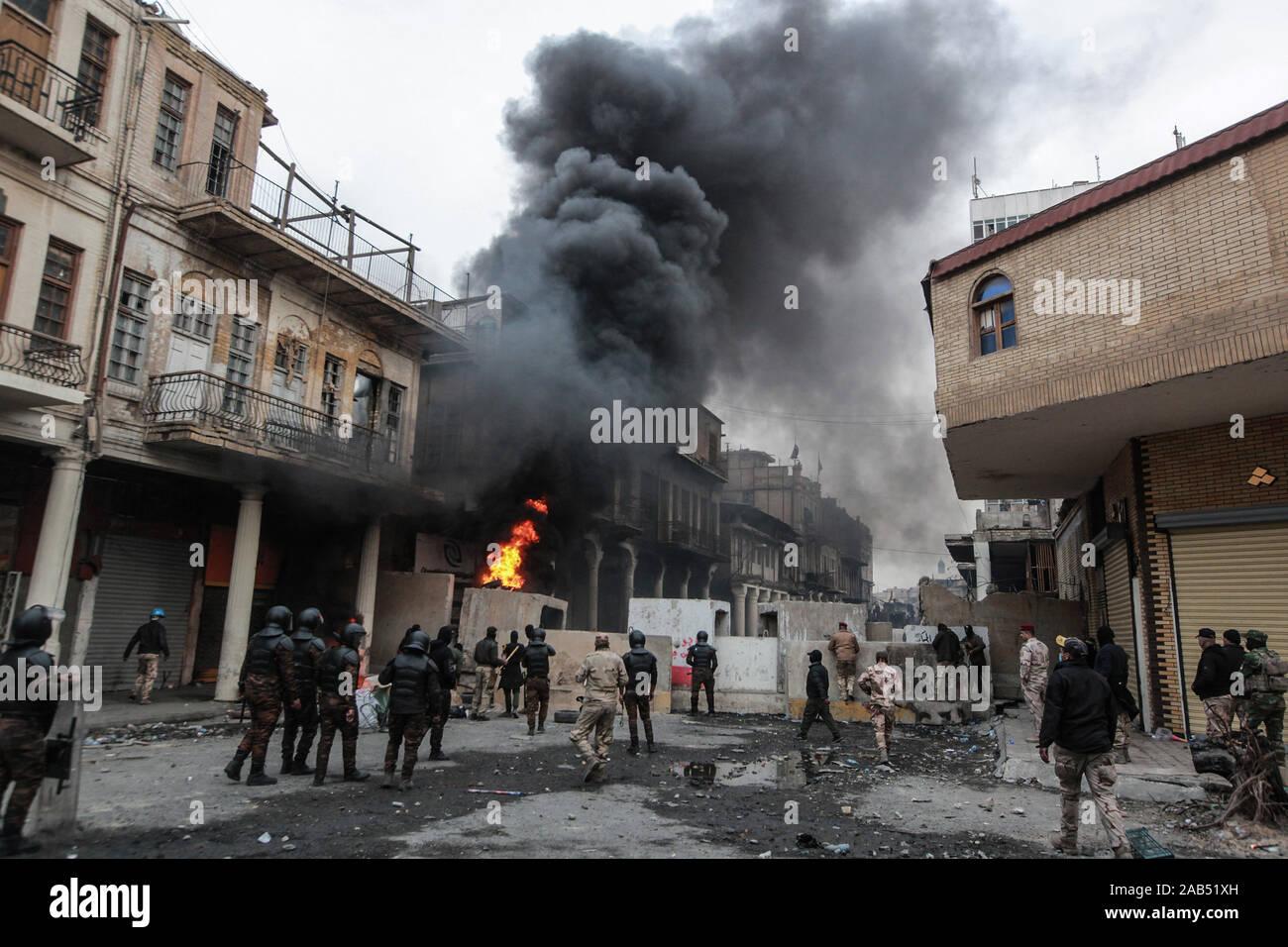 Bagdad, Irak. 25 Nov, 2019. Rauchwolken steigen als Objekte brennen Während der gewalttätigen Auseinandersetzungen zwischen Mitgliedern der irakischen Sicherheitskräfte und regierungsfeindlichen Demonstranten auf Al Rasheed Straße. Credit: Ameer Al Mohammedaw/dpa/Alamy leben Nachrichten Stockfoto