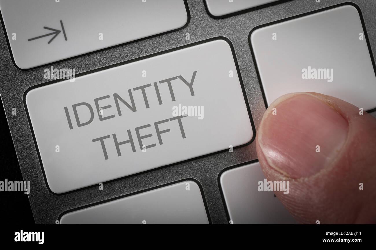 Ein Mann durch Drücken einer Taste auf einer Computertastatur mit den Worten Identitätsdiebstahl. Identität Diebstahl Konzept Bild. Stockfoto