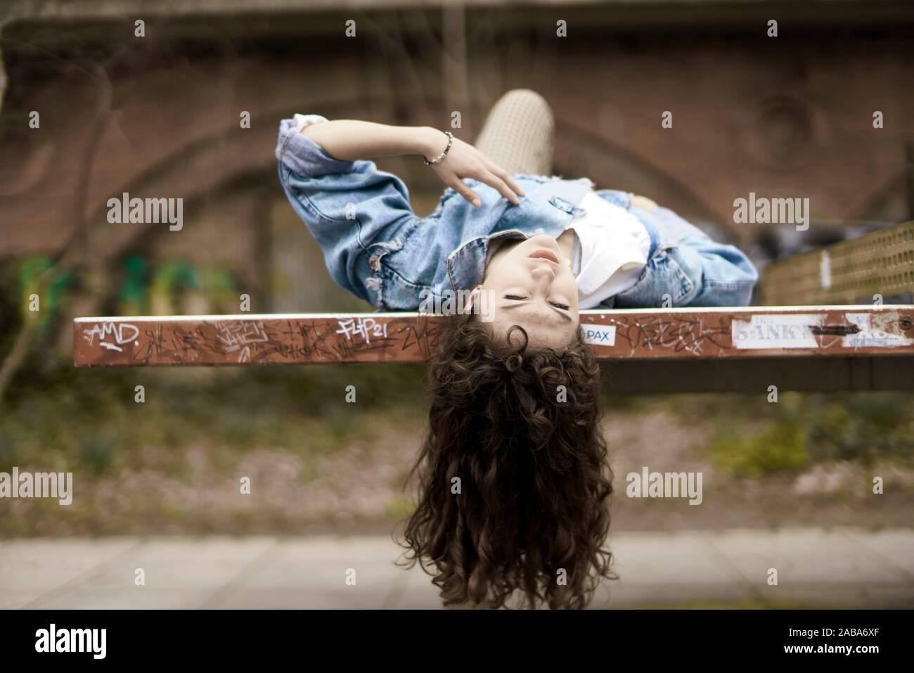 Junge Frau liegend auf der Werkbank, Berlin, Deutschland. Stockfoto