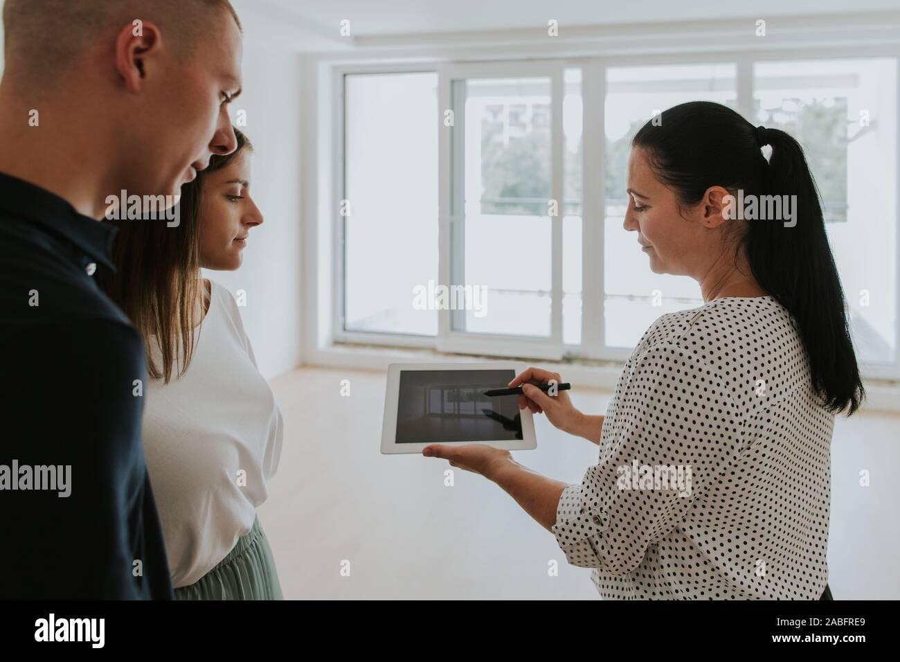 Immobilienmakler mit digitalen Tablet zeigen junge Paar neues Haus Stockfoto