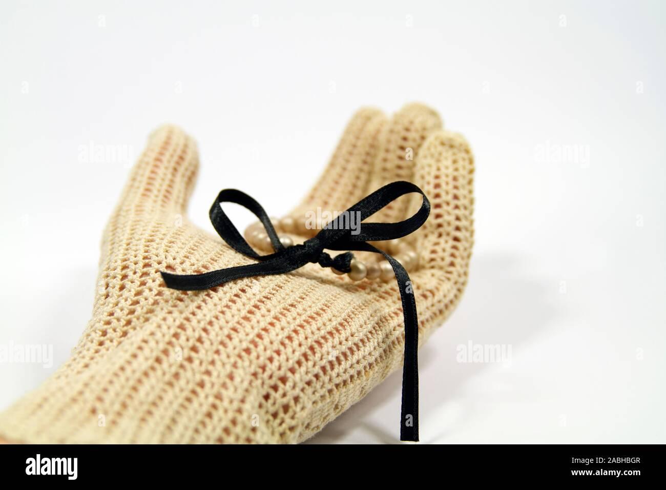 Hand mit Vintage gestricken Handschuh holding Perle Armband mit schwarzem Satinband Stockfoto