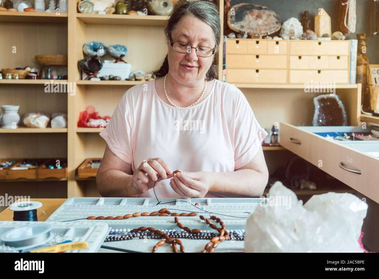 Frau arbeitet an einem Edelstein Halskette als Hobby Stockfoto