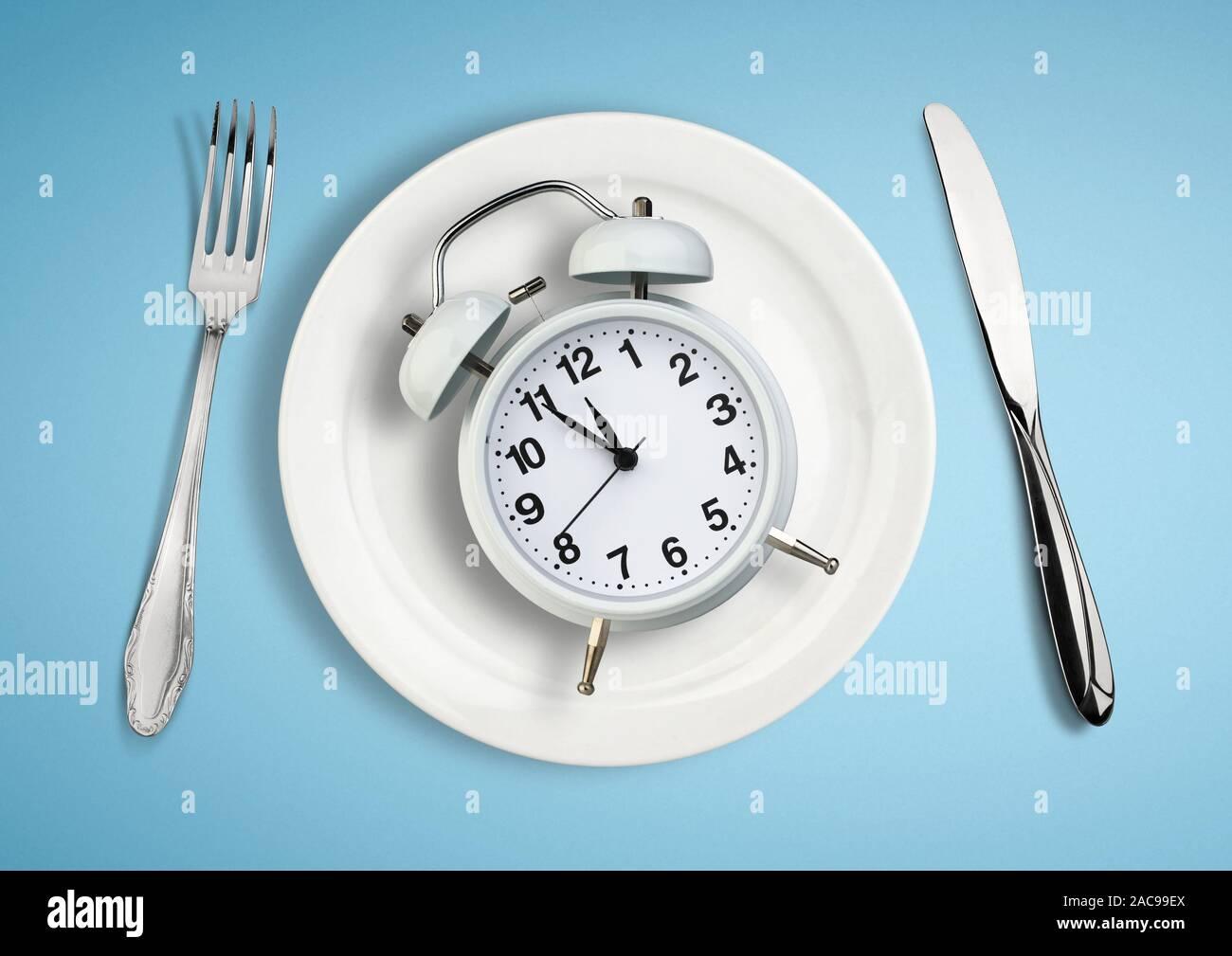 Konzept der intermittierenden Fasten, Mittagszeit, Diät und Gewichtsverlust. Uhr an der Platte. Stockfoto